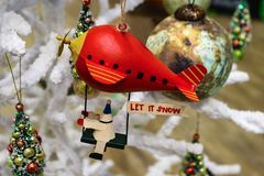 乘坐有让的圣诞节机器人红色软式小型飞艇它下雪在白色蓬松圣诞树的标志 免版税库存照片
