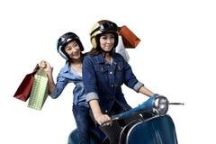 乘坐有购物袋的美丽的两个亚洲人妇女一辆滑行车 图库摄影