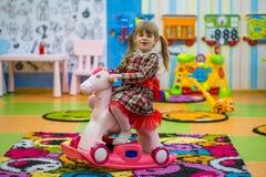 乘坐木马摇摆的愉快的微笑的小女孩 图库摄影