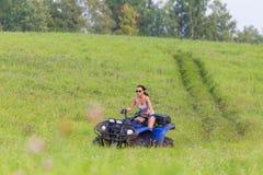 乘坐极端quadrocycle的端庄的妇女 库存照片