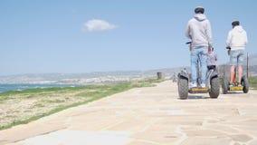 乘坐沿海滩的小组游人segways电滑行车在一个晴朗的大风天 t 股票视频