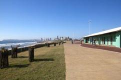 乘坐沿海滩前面散步的三个骑自行车者 免版税库存图片