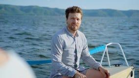 乘坐游艇的一个成人人调整他的衬衣,人半眯着的眼睛他的从太阳的眼睛,明亮地发光  影视素材
