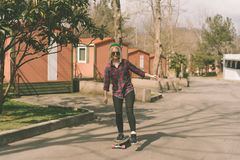 乘坐滑板的白肤金发的行家女孩 免版税库存图片