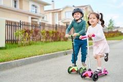 乘坐滑行车的逗人喜爱的孩子 库存图片