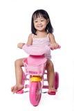 乘坐玩具三轮车的亚裔中国小女孩 免版税库存照片