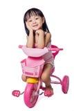 乘坐玩具三轮车的亚裔中国小女孩 免版税图库摄影