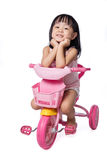 乘坐玩具三轮车的亚裔中国小女孩 库存照片