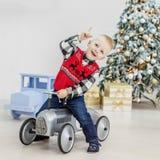 乘坐玩具汽车的小男孩 概念愉快的圣诞节,新年, 免版税库存照片