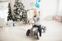 乘坐玩具汽车的愉快的小男孩,在圣诞节装饰的屋子的背景 库存照片