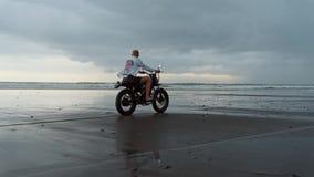 乘坐现代习惯摩托车竟赛者的年轻英俊的行家人在黑沙滩在水附近 冲浪的斑点 影视素材