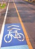 乘坐的自行车标记和箭头方式在柏油路 免版税库存照片