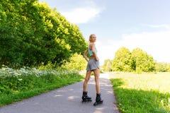 乘坐的直排轮式溜冰鞋的愉快的少妇户外 库存照片