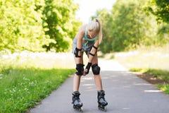 乘坐的直排轮式溜冰鞋的愉快的少妇户外 免版税图库摄影