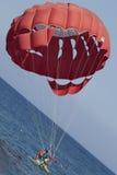乘坐红色帆伞运动的游人夫妇在海附近 库存图片
