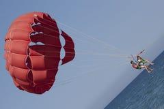 乘坐红色帆伞运动的游人夫妇在海附近 免版税库存照片