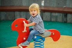 乘坐红色春天车手的逗人喜爱的愉快的男婴 图库摄影