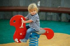 乘坐红色春天车手的逗人喜爱的愉快的男婴 免版税库存图片