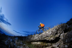 乘坐自行车下来小山的骑自行车者在山岩石足迹在日落 极其体育运动 库存图片