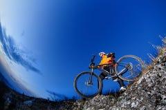 乘坐自行车下来小山的骑自行车者在山岩石足迹在日落 极其体育运动 库存照片