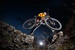 乘坐自行车下来小山的骑自行车者在山岩石足迹在日落 极其体育运动 图库摄影