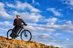 乘坐自行车下来小山的黑夹克的骑自行车者 极端体育概念 文本的空间 免版税库存照片