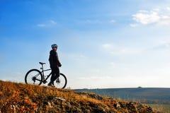 乘坐自行车下来小山的黑夹克的骑自行车者 极端体育概念 文本的空间 库存图片