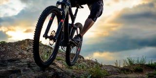 乘坐自行车下来岩石小山的专业骑自行车者在日落 极其体育运动 文本的空间 免版税库存图片