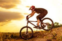 乘坐自行车下来岩石小山的专业骑自行车者在日落 极其体育运动 文本的空间 库存图片