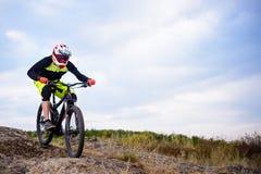 乘坐自行车下来岩石小山的专业骑自行车者 极其体育运动 文本的空间 库存图片