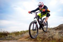 乘坐自行车下来岩石小山的专业骑自行车者 极其体育运动 文本的空间 图库摄影