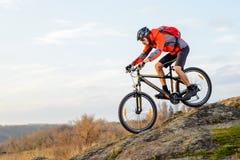 乘坐自行车下来岩石小山的红色夹克的骑自行车者 极其体育运动 免版税库存图片