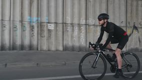 乘坐自行车佩带的盔甲、黑成套装备和太阳镜的确信的适合的被聚焦的骑自行车者 有胡子的自行车车手踩的踏板的自行车 股票录像