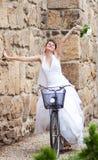 乘坐自行车的愉快的新娘 免版税库存照片