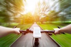 乘坐自行车第一人透视 在把手的智能手机 速度行动迷离 免版税库存照片