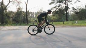 乘坐自行车边跟随看法 黑成套装备的有胡子的人在自行车在公园 出于马鞍踩的踏板 t 影视素材