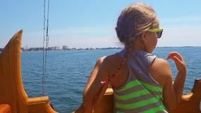 乘坐船的逗人喜爱的女孩在海 太阳镜的女孩少年看从船的城市 少年女孩 股票录像
