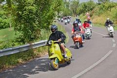 乘坐葡萄酒滑行车Lambretta的骑自行车的人 库存照片