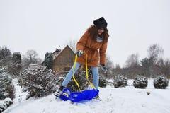 乘坐蓝色雪撬的俏丽的十几岁的女孩 库存图片