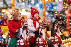 乘坐转盘的孩子在圣诞节市场 免版税库存照片