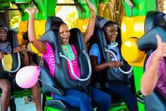 乘坐过山车的青年人在主题乐园 免版税库存图片