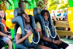 乘坐过山车的青年人在主题乐园 免版税库存照片