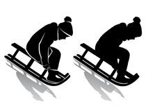 乘坐雪橇的孩子的剪影 图库摄影