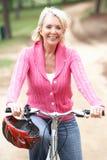 乘坐高级妇女的自行车公园 库存图片