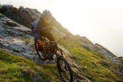 乘坐登山车下来美丽的岩石足迹的Enduro骑自行车者 极端体育概念 文本的空间 库存照片