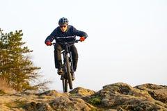 乘坐登山车下来美丽的岩石足迹的Enduro骑自行车者 极端体育概念 文本的空间 免版税库存图片