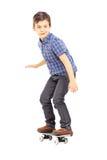 乘坐滑板的一个逗人喜爱的年轻男孩的全长画象 库存照片