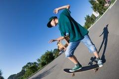 乘坐滑板的快乐的男孩在街道。 免版税库存照片