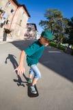 乘坐滑板的男孩在街道。 库存图片