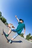 乘坐滑板的男孩在街道。 免版税图库摄影